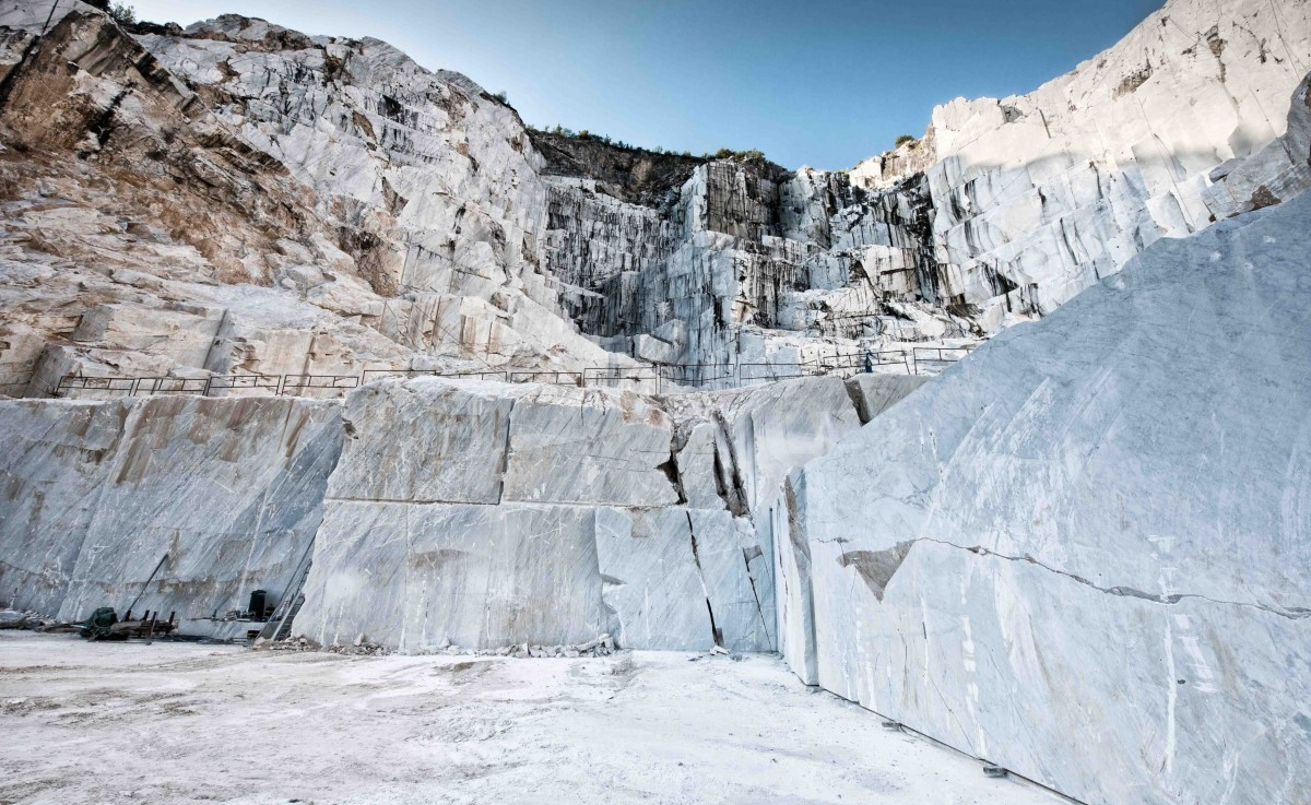 Open cast mining pit for Italian Carrara marble showing the rock face where blocks of rock have been cut and excavated